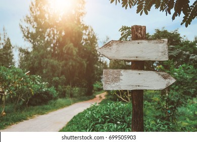 Old wooden road sign with road way background