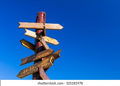 Old wooden road signs with many left and right arrows.
