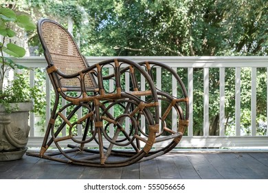 An old wooden rocking chair sitting outside on a dirty front porch