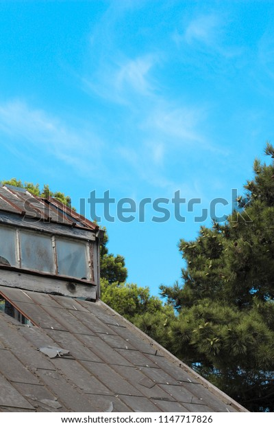 Old wooden roof with the broken windows