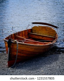Old wooden rowboat on the shore of the Lake District in England
