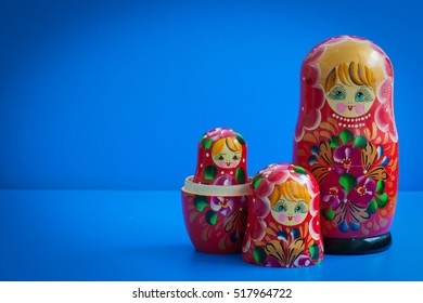 old wooden Russian nesting dolls on a blue background, a symbol of Russia, red, with copy space for text