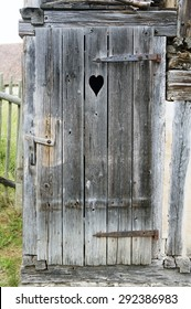 old wooden rustic door with a carved heart