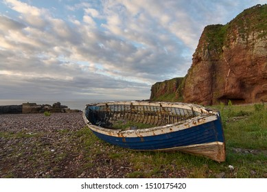 An Old Wooden Scottish Fishing Boat, long abandoned, lies on the Pebble Beach by the Fishing Village of Auchmithie, near Arbroath in Angus, Scotland.