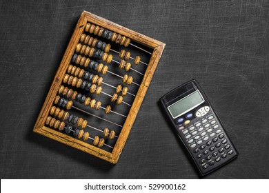 Old wooden scratched vintage decimal abacus and calculator on a black desktop from chalkboard with blank for inscription for the background. Top view. Flat lay. Mockup