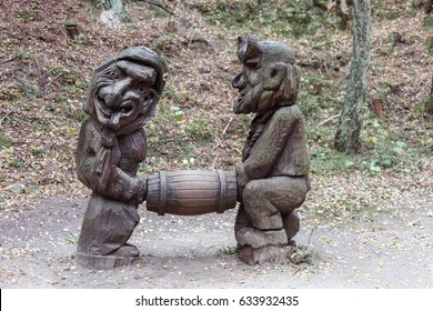 old wooden sculpture in the forest, men carry barrel. Witch Hill park, Lithuania.