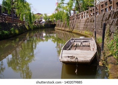 """Old wooden ship, river and willow tree at Sawara, Japan. Sawara is tourist site as it remains old architecture called """"Koedo"""" which means """"Small edo"""". Edo is Japanese old era."""