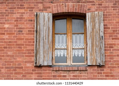 Old Wooden Shutters, Window with Lace Curtains and Brick Building in Europe.
