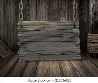 Old wooden sign board on chains