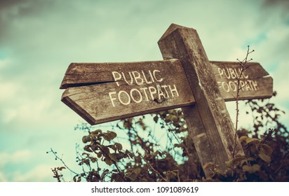 old wooden sign pointing to a public footpath