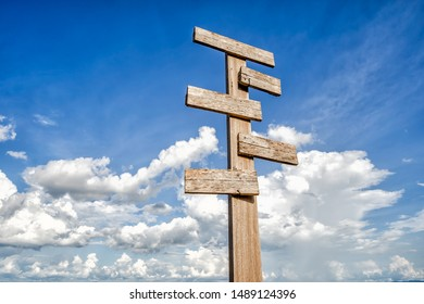 Old wooden signpost against blue sky with five sign choices pointing in different directions.