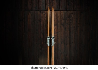 Old wooden skis leaning against a wooden wall