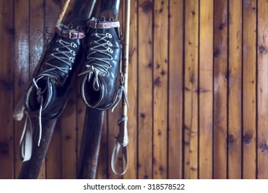 Old wooden skis and leather ski boots on a wooden wall