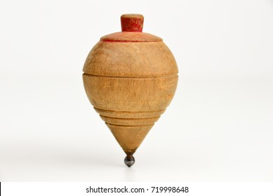 Old wooden spinning top on against a white background