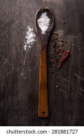 Old wooden spoon, salt and chilly pepper on vintage background. Tabletop view.