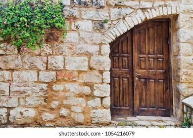 Old wooden studded door set in a heavy stone wall with climbing plants and flowers, Jerusalem, Israel