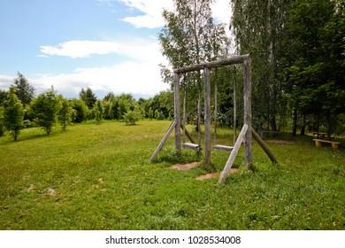 Old wooden swing in the green field in village, Belarus.