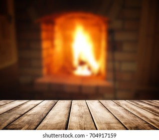 Old wooden table and blurred background of fireplace