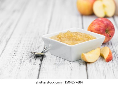 Old wooden table with fresh made Applesauce (selective focus; close-up shot)