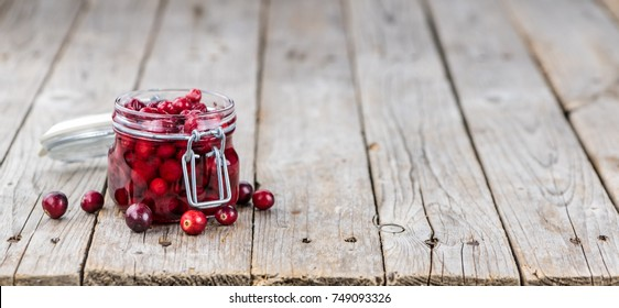 Old wooden table with fresh Preserved Cranberries (close-up shot; selective focus)
