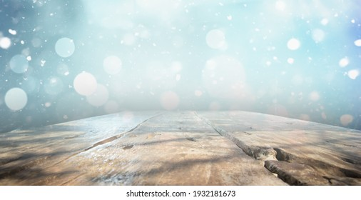 OLD WOODEN TABLE ON BLUE SNOWY BOKEH LIGHTS, NATURAL CHRISTMAS BACKDROP FOR MONTAGE OR DISPLAY WINTER PRODUCTS OR CHRISTMAS PRESENTS