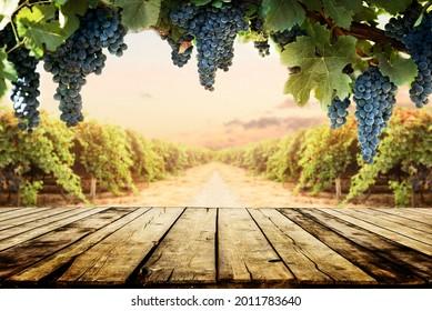 Vieille table en bois sur fond vintage flou et raisin. Tablette de produits viticoles design nature. Bannière de mise en page de l'exposition de la vaisselle.