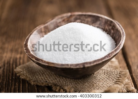 Old wooden table with white Sugar (selective focus; close-up shot)