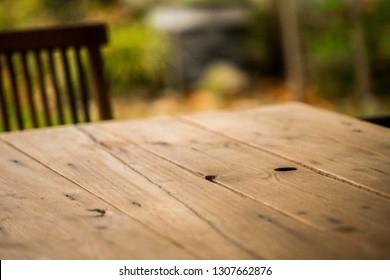 Old wooden tabletop with some cracks, beautiful wood grain and knotholes. A teak chair, plants and a plant pot in the backround.