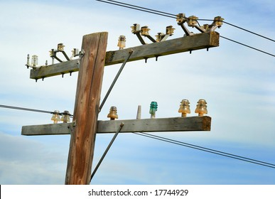 Old wooden telephone pole with vintage glass insulators.