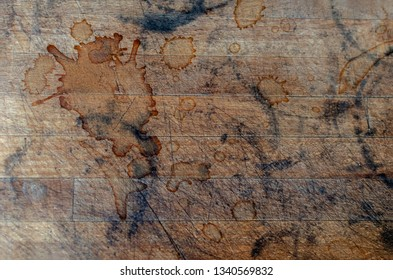 Old wooden textured background with scratches, black marks and coffee spots.