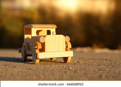 old wooden toy car on the road outdoors in the park at sunset. nostalgia and simplicity concept