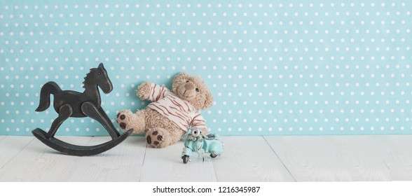 Old wooden toy horse rocking chair, teddy bear and blue vintage motorcycle in baby's room on blue background