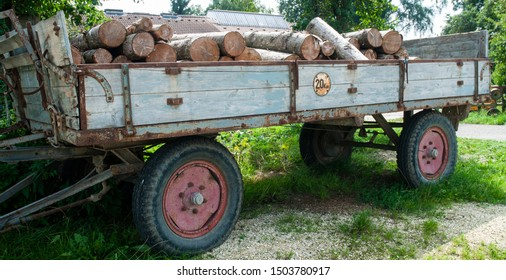 old wooden trailer on farmyard with rusty speed restriction sign and woodpile as cargo