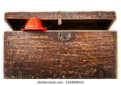 Old wooden trunk with modern red christmas hat keeping the coffer open isolated on white