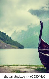 Old wooden viking boat on seashore in norwegian nature, foggy misty day. Mountains and fjord Sognefjord. Tourism and traveling concept
