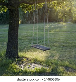 Old Wooden Vintage Garden Swing Hanging From A Large Tree On Green Grass  Background, In