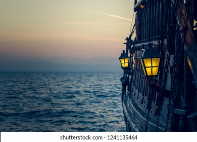old wooden vintage pirate ship on sea water surface in sunset evening romantic time with yellow light from soft focus lantern in overboard space