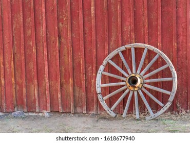 Old wooden wagon wheel leaning up against the side of an old red barn. Horizontal photo format.