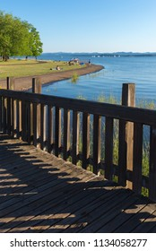 An old wooden walkway leads to a park by a lake