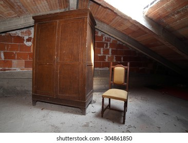 old wooden wardrobe and an antique chair in the dusty attic