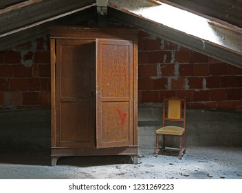 old wooden wardrobe and a chair in the uninhabited attic