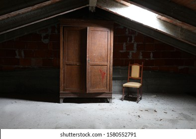 old wooden wardrobe and a vintage chair in the dusty attic without people