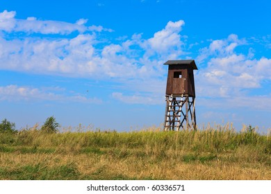 Old wooden watch tower in a field stubble with blue sky background