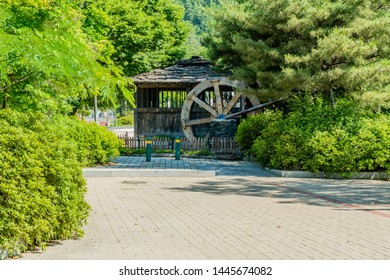 Old wooden water wheel and mill house at edge of tree lined parking lot at public park in South Korea.
