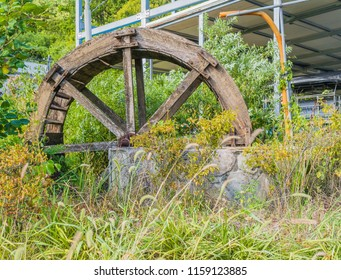 Old wooden water wheel surrounded by overgrown grass and weeds in front of metal structure in rural community.