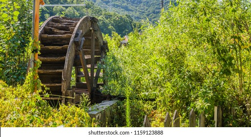 Old wooden water wheel that has fallen into state of disrepair surrounded by overgrown grass and weeds