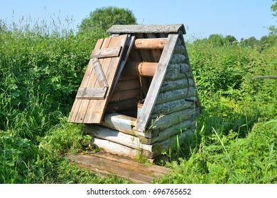 Old wooden well among the tall grass