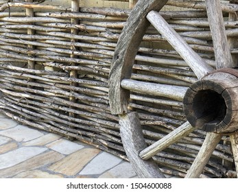 Old wooden wheel from a cart horse. The wheel of a wooden stroller since ancient times. Scenery in the yard: a wheel made of wood against the background of a fence made of branches.