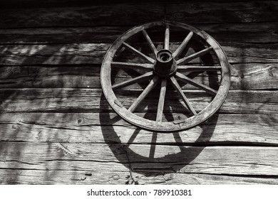 Old wooden wheel on the wall of an antique wooden barn, black and white photo