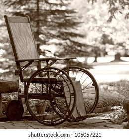 Old wooden wheelchair sits waiting in the garden